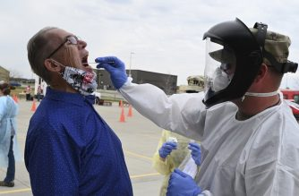 "This US Air National Guard photo obtained April 28, 2020 shows Maj. Preston Schaffner, of the 81st Civil Support Team(R), taking a swab sample from Scott Hennen who is an asymptomatic volunteer to taking a COVID-19 test in the parking lot of the FaroDome, in Fargo, North Dakota on April 25, 2020. - Schaffner is wearing personal protective equipment (PPE) to stay safe while he works and helps prevent the spread of the Coronavirus while testing people as they drive through the mass testing process in their vehicles. He is just one of the North Dakota National Guard members partnering with the North Dakota Department of Health and other civilian agencies in support of the whole community response to the COVID-19 pandemic. (Photo by David H. LIPP / Air National Guard / AFP) / RESTRICTED TO EDITORIAL USE - MANDATORY CREDIT ""AFP PHOTO /AIR NATIONAL GUARD/DAVID H. LIPP/HANDOUT "" - NO MARKETING - NO ADVERTISING CAMPAIGNS - DISTRIBUTED AS A SERVICE TO CLIENTS"