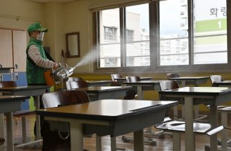 A worker sprays disinfectant in a classroom at a high school in Seoul on May 19, 2020. - South Korea has been held up as a global model in how to curb the coronavirus, but a spike of new cases, driven by a nightclub cluster in Seoul's Itaewon district -- including several gay clubs -- forced authorities to delay last week's planned re-opening of schools for a week. (Photo by Jung Yeon-je / AFP)