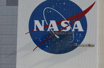 Painters refurbish the NASA logo on the Vehicle Assembly Building at the Kennedy Space Center in Florida in Florida on May 29, 2020. The faded 10-story-tall insignia was last painted 13 years ago. - The SpaceX Falcon 9 rocket with the Crew Dragon capsule is rescheduled to launch to the International Space Station on May 30, carrying astronauts Bob Behnken and Doug Hurley. (Photo by Gregg Newton / AFP)