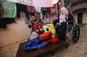 Nihad Jarboa, 37, and his wife Zeinab, 35, Palestinians living with a physical handicap since their childhood, sit on their wheelchairs as the stitch cartoon-inspired costumes at their home in the Rafah refugee camp in the southern Gaza Strip, on July 19, 2020. - The husband and wife live with their two children in a single-room home, and sell  handmade costumes to earn a living under harsh economic conditions in the coastal enclave, under an Israeli-enforced blockade since 2007. (Photo by SAID KHATIB / AFP)