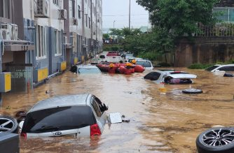 Rescue workers search near vehicles in a parking lot and lower sections of apartment buildings flooded due to heavy rain in Daejeon on July 30, 2020. (Photo by - / YONHAP / AFP) / - South Korea OUT / REPUBLIC OF KOREA OUT  NO ARCHIVES  RESTRICTED TO SUBSCRIPTION USE