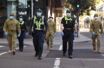 A group of police and soldiers patrol the Docklands area of Melbourne on August 2, 2020, after the announcement of new restrictions to curb the spread of the COVID-19 coronavirus. - Australia on August 2 introduced sweeping new measures to control a growing coronavirus outbreak in its second-biggest city, including an overnight curfew and a ban on weddings for the first time during the pandemic. (Photo by William WEST / AFP)