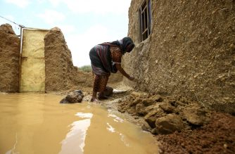 A Sudanese woman repairs damages to her house, after torrential rain lead to landslides and flash floods, in the town of Umm Dawan Ban, southeast of the capital Khartoum on August 2, 2020. (Photo by ASHRAF SHAZLY / AFP)