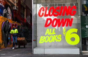 A worker walks past a empty shop in Melbourne's central business district on August 3, 2020 after the state announced new restrictions as the city battles fresh outbreaks of the COVID-19 coronavirus. - Australia's Victoria state imposed fresh, sweeping restrictions on August 2, 2020, including a curfew in Melbourne for the next six weeks, a ban on weddings, and schools and universities going back online in the coming days. (Photo by William WEST / AFP)