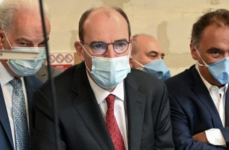 French Prime Minister Jean Castex (C), flanked by French Junior Minister of Small and Medium Entreprises Alain Griset (L) looks on during a visit to a mask making workshop in Roubaix, northern France, on August 3, 2020, as mask-wearing becomes mandatory in the the city centre amid concerns about an increase in COVID-19 (novel coronavirus) cases. (Photo by DENIS CHARLET / AFP)