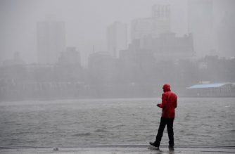 A man stands near the East River in lower Manhattan as Tropical Storm Isaias approaches New York City on August 4, 2020. - Isaias pounded the US eastern seaboard with driving rain and strong winds on Tuesday, leaving hundreds of thousands without power and prompting flood precautions in New York City. (Photo by Angela Weiss / AFP)