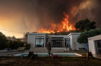 A man walks with a garden hose to drench his house before being evacuated as a wild fire burns in the background, in La Couronne, near Marseille, on August 4, 2020. - Several fires were raging on August 4 evening near Marseille, with one particularly fuelled by strong winds, ravaging nearly 300 hectares of vegetation in a coastal area of Martigues, according to the authorities. (Photo by Xavier LEOTY / AFP)