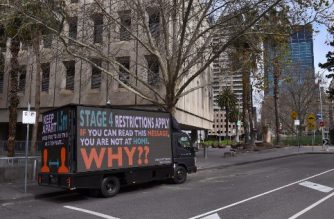 A sign on a truck warns people to stay home in Melbourne on August 5, 2020, as the city enforces strict lockdown restrictions after a fresh outbreak of the COVID-19 coronavirus. - Australia's worst-hit state of Victoria reported 725 new cases and 15 coronavirus deaths on August 5, including a man in his 30s, making it the country's deadliest day of the pandemic to date. (Photo by William WEST / AFP)