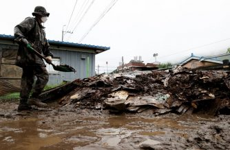 A soldier shovels debris left by flood damage following heavy rain fall in Saengchang village in Cheorwon on August 6, 2020. (Photo by - / YONHAP / AFP) / - South Korea OUT / REPUBLIC OF KOREA OUT  NO ARCHIVES  RESTRICTED TO SUBSCRIPTION USE