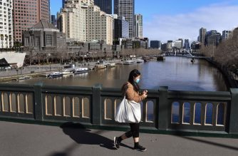 A woman crosses the Yarra River in the central business district in Melbourne on August 6, 2020. - Australia's second city Melbourne entered a more restrictive six-week lockdown on August 6, sparking a fresh wave of anxiety and confusion over ever-tougher regulations. (Photo by William WEST / AFP)