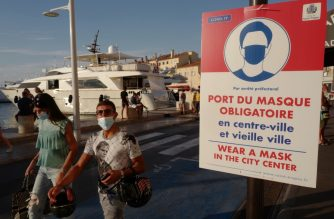 People wearing face masks walk past an information sign, along  Saint-Tropez harbour on August 8, 2020, as the city made wearing a protective mask mandatory in the town center. (Photo by Valery HACHE / AFP)
