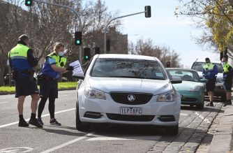 Police officers pull a car over for a licence and permit check in Melbourne on August 11, 2020, during a strict stage four lockdown of the city due to a COVID-19 coronavirus outbreak. - Victoria state reported 19 deaths from coronavirus on August 11, making it the country's equal deadliest day of the pandemic despite a fall in new case numbers. (Photo by William WEST / AFP)