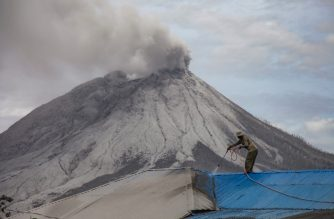 A villager cleans volcanic ash from his roof at Naman Teran village in Karo, North Sumatra, on August 11, 2020 a day after the eruption of Mount Sinabung (background). (Photo by IVAN DAMANIK / AFP)