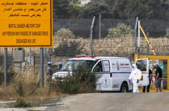 A health worker wearing PPE (personal protective equipment) due to the COVID-19 coronavirus pandemic, walks past UN peacekeepers standing by the ambulance transporting Wafaa Nasrallah, daughter of the last remaining indigenous Orthodox Christian family in the Israeli-annexed Golan Heights, at the United Nations Quneitra crossing with Syria on August 11, 2020. - Nasrallah left her home in the Golan's Majdal Shams in 1995 to pursue a university degree in Damascus and afterwards chose to remain there. After falling into a coma three years prior, her family struggled to obtain the necessary permits for her return via the Quneitra crossing which was shut due to the ongoing civil war in Syria. Nasrallah's family was last able to see her in 2007 when she was allowed to visit her hometown. (Photo by JALAA MAREY / AFP)