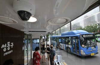 People wait for buses in a shelter booth designed to protect passengers from monsoon rains, summer heat and the COVID-19 coronavirus in Seoul on August 12, 2020. - Automatic temperature checks before entry, sliding doors and an air-conditioning system equipped with ultraviolet disinfection lamps -- welcome to high-tech South Korea's latest front in the battle against coronavirus: the bus shelter. (Photo by Jung Yeon-je / AFP)