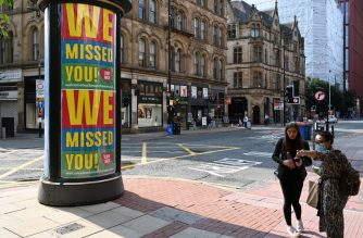 "A woman (R) wearing a face mask or covering due to the COVID-19 pandemic, asks for directions near a billboard with a poster telling shoppers ""We've Missed You!"" in Manchester, northern England on August 12, 2020. - Britain's economy contracted by a record 20.4 percent in the second quarter with the country in lockdown over the novel coronavirus pandemic, official data showed Wednesday.  ""It is clear that the UK is in the largest recession on record,"" the Office for National Statistics said. Britain officially entered recession in the second quarter after gross domestic product (GDP) contracted by 2.2 percent in the first three months of the year. (Photo by Paul ELLIS / AFP)"