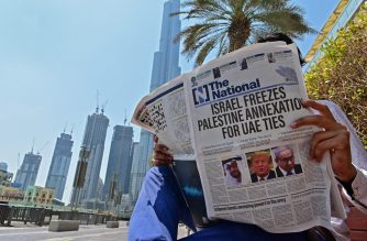 """A man reads a copy of UAE-based The National newspaper near the Burj Khalifa, the tallest structure and building in the world since 2009, in the gulf emirate of Dubai on August 14, 2020, as the publication's headline reflects the previous day's news as Israel and the UAE agreed to normalise relations in a landmark US-brokered deal. - The deal marks only the third such accord the Jewish state has struck with an Arab nation, an historic shift making the Gulf state only the third Arab country to establish full diplomatic ties with the Jewish state. The Palestinian leadership voiced its """"strong rejection and condemnation"""" of the deal and announced it would withdraw its envoy from the UAE, and Turkey also condemned the deal as an act of treachery. (Photo by Giuseppe CACACE / AFP)"""