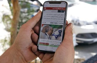"""A man holds a phone while reading a story published on Tasnim News Agency's website about the recent news of a US-brokered deal between Israel and the UAE to normalise relations, in Iran's capital Tehran on August 14, 2020. - Iran strongly condemned the agreement, blasting it as an act of """"strategic stupidity"""" that would only strengthen the Tehran-backed """"axis of resistance"""". The Israel-UAE deal marks only the third such accord the Jewish state has struck with an Arab nation, an historic shift making the Gulf state only the third Arab country to establish full diplomatic ties with the Jewish state. (Photo by - / AFP)"""