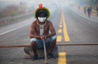 A member of the Kayapo tribe sits after they blocked highway BR163 during a protest on the outskirts of Novo Progresso in Para State, Brazil, on August 18, 2020 amid the COVID-19 novel coronavirus pandemic. - Brandishing bows and arrows, dozens of indigenous protesters blocked a main highway through the Brazilian Amazon, demanding help against the new coronavirus and an end to illegal mining and deforestation. (Photo by JOÃO LAET / AFP)