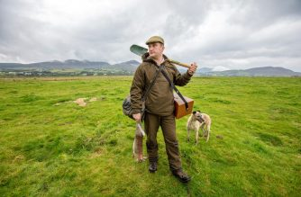 Professional rabbit catcher Steven McGonigal, poses for a photograph with his dog Fudge, and a 'dispatched' our caught rabbit, as he hunts for rabbits in County Donegal, northwest Ireland, on August 18, 2020. - McGonigal is said to be Ireland's last traditional rabbit catcher, preferring ferrets, dogs, spades and nets instead of modern guns and poison. (Photo by Paul Faith / AFP)