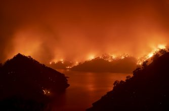 Flames surround Lake Berryessa during the LNU Lightning Complex fire in Napa, California on August 19, 2020. - Thousands of people fled their homes in northern California on August 19 as hundreds of fast-moving wildfires spread across the region, burning houses and leading to the death of a helicopter pilot. (Photo by JOSH EDELSON / AFP)