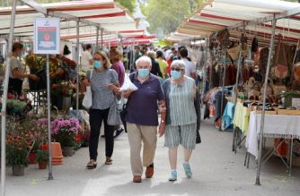 "People wearing face masks walk at a market in Paris, on August 27, 2020, as face masks will become mandatory in the city. - France's prime minister on August 27 announced face masks will become compulsory throughout Paris, expressing concern over an ""undeniable"" trend of expanding coronavirus infection in the country. Jean Castex said 19 more departments have been added to a map with ""red"" zones of active virus circulation, meaning 21 of France's 94 departments are classified as such. Official figures released on August 26 showed more than 5,400 confirmed new cases in just 24 hours, with admissions to hospital and intensive care units on the rise. (Photo by Ludovic MARIN / AFP)"