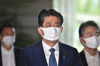 Japan's Prime Minister Shinzo Abe (C) wearing a face mask arrives at the prime minister's office in Tokyo on August 28, 2020. - Japan's Prime Minister Shinzo Abe is to announce his resignation over health issues, local media reported on August 28 hours before he is due to address a press conference. (Photo by Kazuhiro NOGI / AFP)