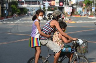 A father with his children aboard their bicycle crosses an almost empty road in Manila on March 20, 2020, after the government imposed an enhanced community quarantine against the rising numbers of COVID-19 coronavirus infections. - Philippine President Rodrigo Duterte ordered about half the country's population to stay home for the next month in a drastic bid March 16 to curb the rising number of new coronavirus cases. (Photo by Ted ALJIBE / AFP)