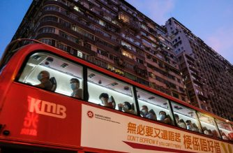 Commuters wear face masks as they travel on a double decker bus in Hong Kong on July 15, 2020, as the city experiences another spike in COVID-19 coronavirus cases. - Hong Kong reimposed tough social distancing measures on July 15 -- shuttering many businesses and making facemasks on public transport mandatory -- after a spike in coronavirus cases threatens to undo months of success against the disease. (Photo by Anthony WALLACE / AFP)