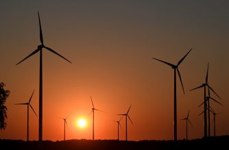 Sun sets behind wind turbines near the small villages of Neu Zauche and Straupitz, eastern Germany, at the end of a hot summer day on August 11, 2020. (Photo by Christof STACHE / AFP)