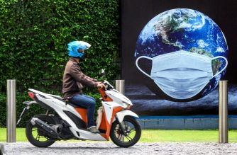 A man rides his scooter in front of a COVID-19 coronavirus related poster  in Bangkok on August 20, 2020. (Photo by Mladen ANTONOV / AFP)