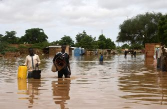 People carry their belongings while walking in a street flooded by the waters from the Niger river that flooded in the Kirkissoye neighbourhood in Niamey on August 27, 2020. (Photo by BOUREIMA HAMA / AFP)