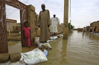 Sudanese residents walk on sandbags to reach their houses along a flooded street in the capital Khartoum's southern neighbourhood of al-Kalakla, on August 31, 2020. (Photo by ASHRAF SHAZLY / AFP)