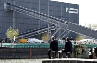 (FILES) This file photo taken on April 7, 2014 shows people sitting along the river, across from the French cement company Lafarge-Holcim, in  Paris. - Hundreds of litres of toxic wastewater have leaked into Paris' Seine River from a plant belonging to Franco-Swiss cement giant Lafarge-Holcim, local reports said sparking outrage from French officials. Lafarge acknowledged the spillage but insisted it had been the result of sabotage, rather than an intentional act by the company. Paris prosecutors told AFP they had opened an investigation into pollution of the river with harmful products on August 27, 2020. (Photo by Franck FIFE / AFP)
