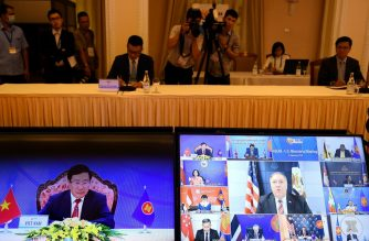 """Vietnam's Foreign Minister Pham Binh Minh (L) and US Secretary of State Mike Pompeo (C, on screen at R) are seen on monitor screens during the Association of Southeast Asian Nations (ASEAN)-US Ministerial Meeting, held online due to the COVID-19 novel coronavirus pandemic, in Hanoi on September 10, 2020. - China accused the US of becoming """"the biggest driver of militarization"""" in the contested South China Sea, as tensions between Washington and Beijing look set to swamp a regional Asian summit. (Photo by Nhac NGUYEN / AFP)"""