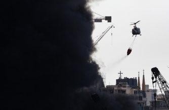 A Lebanese army helicopter pours water over a huge fire in the capital Beiru'st seaport on September 10, 2020. - Clouds of dark smoke spilled into the sky above the capital, and were visible from its suburbs, after the army said the fire broke out in a warehouse containing oil and tyres. (Photo by ANWAR AMRO / AFP)