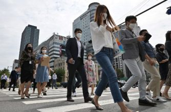 People wearing face masks cross a road in Seoul on September 11, 2020. - South Korea largely overcame an early COVID-19 coronavirus outbreak with extensive tracing and testing, but is now battling several outbreaks. (Photo by Jung Yeon-je / AFP)