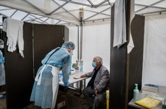 Medical staff with protective gear speaks with a man as he conducts tests for Covid-19, on September 11, 2020 in Venissieux, near Lyon, amid the novel coronavirus pandemic. (Photo by JEFF PACHOUD / AFP)