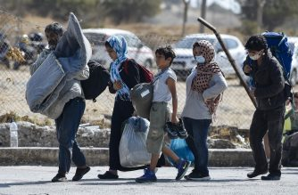 A family carrying their belongings walk toward a new temporary camp, set up to shelter refugees from the burnt Moria refugee camp, on the island of Lesbos on September 13, 2020, a few days after a fire destroyed the camp. - Greece said on September 13 it hoped thousands of asylum seekers left homeless by fires at Europe's largest migrant camp could be rehoused within a week to end a crisis that has seen clashes with police. Asylum-seekers, including the elderly and very young children, have been sleeping rough on Lesbos island since September 9, when some 11,000 fled the overcrowded Moria camp after it was gutted in apparent arson attacks. (Photo by LOUISA GOULIAMAKI / AFP)