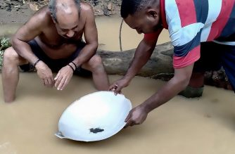 This picture taken on July 7, 2020 shows two miners panning for gold along a stream near Korowai, Papua province. - Illegal mining has soared across Indonesia's restive Papua region in the midst of the global health crisis, despite hazards including the risk of arrest and health damage from toxic mercury used at many makeshift mining sites. (Photo by Efert ABUBAR / AFP) / TO GO WITH Indonesia-mining-environment-health-virus,FOCUS by Helena Kobogau and Haeril Halim