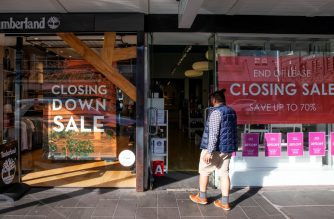(FILES) In this file photo taken on June 19, 2020 a shopper makes his way into a store offering a closing down sale in Auckland. - New Zealand's economy plunged into recession for the first time in a decade on September 17, 2020, posting a record contraction in the June quarter due to the coronavirus pandemic, as Prime Minister Jacinda Ardern heads into next month's general election. (Photo by GREG BOWKER / AFP)