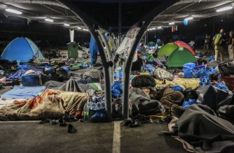 Migrants find shelter at a supermarket parking lot on September 17, 2020 in Lesbos before Police began an operation to rehouse thousands of homeless migrants at a new site after their camp was destroyed by fire last week. (Photo by - / AFP)