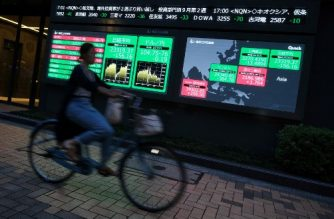 A bicycle rider passes an electronic quotation board displaying share prices of the Tokyo Stock Exchange (2nd L) and numbers of Asian markets in Tokyo on September 17, 2020. - Japan's central bank on September 17 said it would maintain its ultra-loose monetary policy as the virus-hit economy gradually picks up, with no big changes announced the day after new Prime Minister Yoshihide Suga took office. (Photo by Kazuhiro NOGI / AFP)