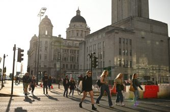 People walk in the early evening sunshine on the Pier Head in Liverpool, north-west England on September 18, 2020 after the British government imposed fresh restrictions on the city after an rise in cases of the novel coronavirus. - Millions more people in northern and central England faced new restrictions over a surge in coronavirus cases, the British government announced on Friday, as it warned another national lockdown could be imminent. Tighter regulations preventing people from socialising with anyone outside their household will come into force from next Tuesday across parts of the northwest, the Midlands and West Yorkshire. Food and drink venues in the northwestern areas of Merseyside, Warrington, Halton and Lancashire will be restricted to table service only, while pubs and bars will have to shut early by 10:00 pm (2100 GMT). (Photo by Oli SCARFF / AFP)
