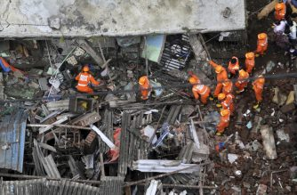 Rescue workers search for survivors in the rubble of a collapsed three-storey residential building in Bhiwandi on September 21, 2020. - Ten people were killed and up to 25 were feared trapped after a three-storey residential building collapsed before dawn on September 21 in western India, officials said. (Photo by - / AFP)