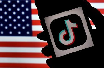(FILES) In this file photo illustration taken on August 3, 2020, the social media application logo, TikTok is displayed on the screen of an iPhone on an US flag as the background in Arlington, Virginia. - President Donald Trump on September 21, 2020 threw into doubt a deal to restructure ownership of the popular video app TikTok, vowing to block any deal that allows its Chinese parent firm to retain any control.The comments raised fresh concerns over a weekend deal that appeared to avert a US-ordered ban of TikTok, which the Trump administration has called a national security risk. (Photo by Olivier DOULIERY / AFP)