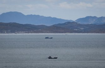 "This photo taken on April 24, 2018 shows a general view of unidentified fishing boats before the North Korean coastline from a viewpoint on the South Korea-controlled island of Yeonpyeong near the disputed waters of the Yellow Sea at dawn. - North Korean forces shot dead a Southern fisheries official who disappeared off a patrol vessel and ended up in Pyongyang's waters, Seoul's defence ministry said on September 24, 2020, calling it an ""outrageous act"". (Photo by Ed JONES / AFP)"