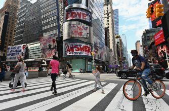 """People cross the street near Time Square on September 28, 2020 in New York City. - Coronavirus infection rates have increased at """"an alarming rate"""" in several New York neighbourhoods, particularly among the Orthodox Jewish community in Brooklyn, city health authorities warned Sunday, threatening to sanction certain schools if they fail to comply with anti-virus regulations. (Photo by Angela Weiss / AFP)"""