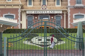 (FILES) In this file photo taken on March 14, 2020 an employee cleans the grounds behind the closed gates of Disneyland Park on the first day of the closure of Disneyland and Disney California Adventure theme parks as fear of the spread of coronavirus continue, in Anaheim, California. - Disney announced September 29, 2020, it will cut 28,000 jobs from its US parks and experiences division, pointing to depressed demand caused by the coronavirus and uncertainty on when it will recover. (Photo by DAVID MCNEW / AFP)
