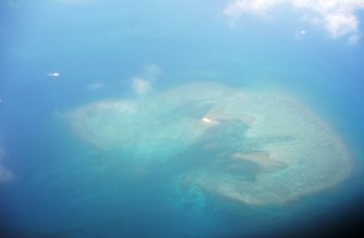 This picture taken on April 21, 2017 shows an aerial view of a reef near the island of Thitu, with what are believed to be anchored Chinese boats, in the disputed Spratly islands. - Philippine Defence Secretary Delfin Lorenzana flew to a disputed South China Sea island on April 21, brushing off a challenge by the Chinese military while asserting Manila's territorial claim to the strategic region. (Photo by Ted ALJIBE / AFP)